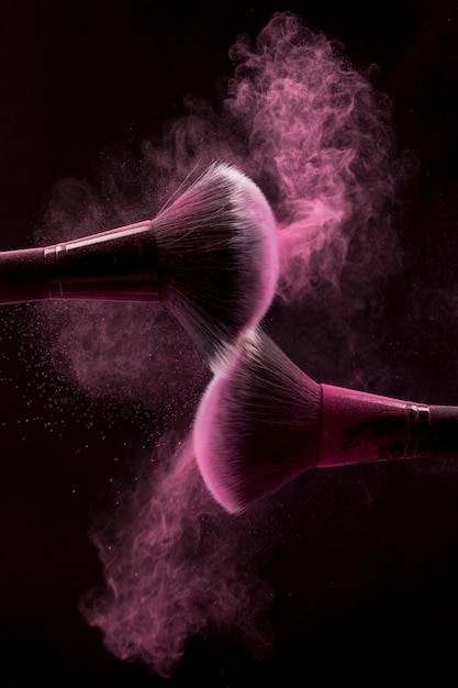 Cosmetic brushes in pink mist of powder on dark background Free Photo