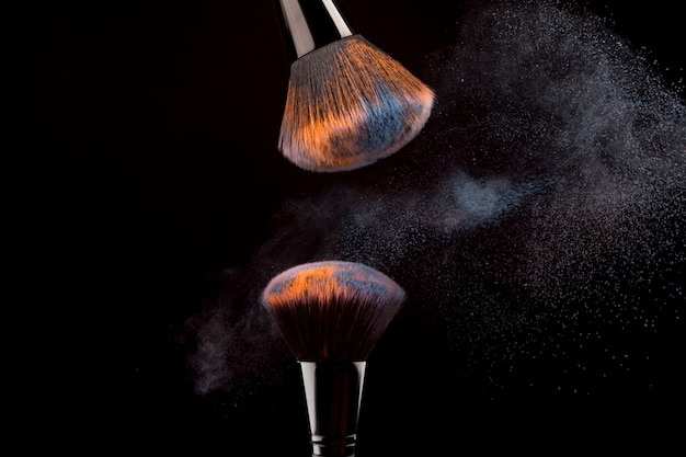 Cosmetic brushes with mist of powder on dark background Free Photo