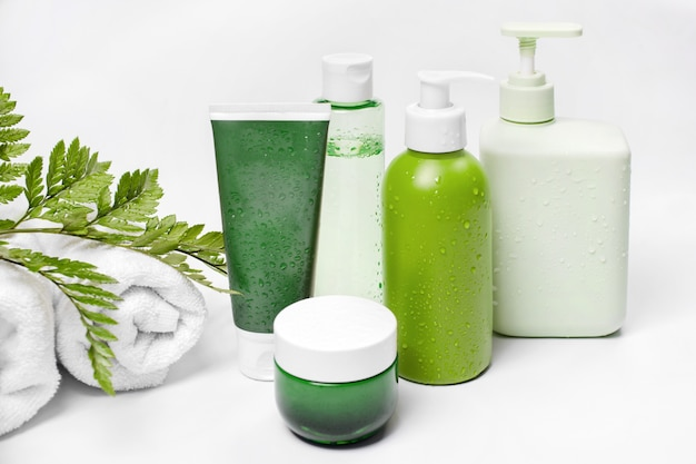 Cosmetic containers with green herbal leaves and white towels, blank label package for branding mock-up. moisturizing cream, shampoo, tonic, face and body skin care. Premium Photo