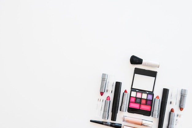 Cosmetic eye shadows; different shades of lipstick; and brush arranged on white background Free Photo