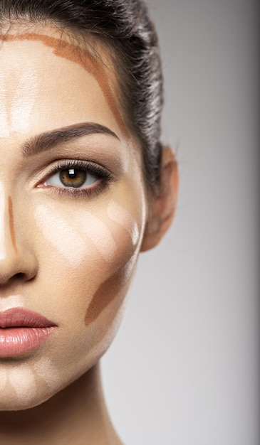 화장품 메이크업 색조 파운데이션은 여성의 얼굴에 있습니다. 미용 치료 개념. 소녀는 메이크업을합니다. 무료 사진
