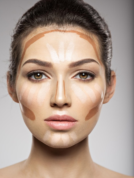 Cosmetic makeup tonal foundation is on woman's face. beauty treatment concept. girl makes makeup. Free Photo