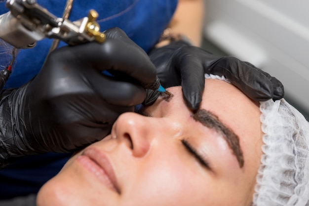 Cosmetic procedures for the treatment of eyebrows. microblading in the beauty salon. professional cosmetology. the process of applying the pigment,shaping eyebrows.permanent makeup eyebrows, tattooing Premium Photo