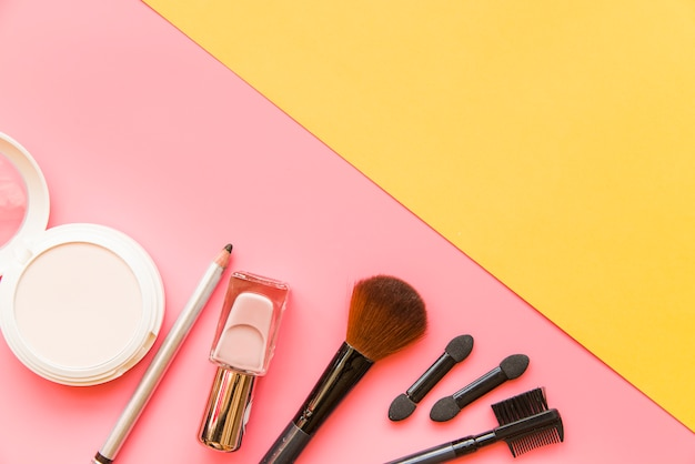 Cosmetic product with brushes on pink and yellow dual background Free Photo