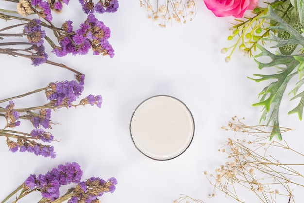 Cosmetic products and flowers on white Free Photo