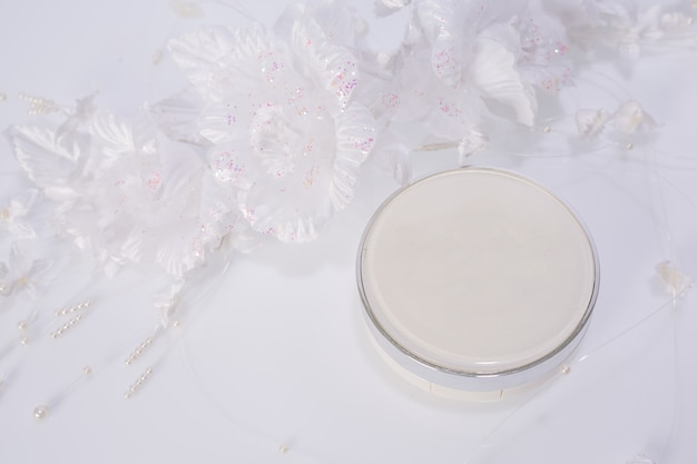 Cosmetic products and flowers on white Photo | Free Download