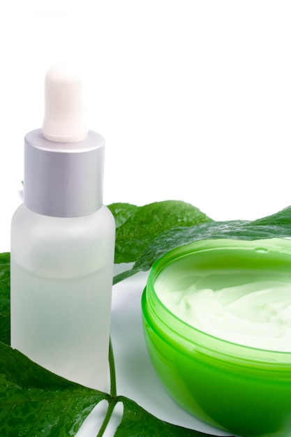 Cosmetic products with green leaf on white background Premium Photo