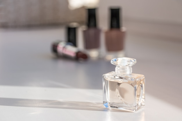 Cosmetic set. nail polish, lipsticks and perfume. selective focus on front bottle. Premium Photo