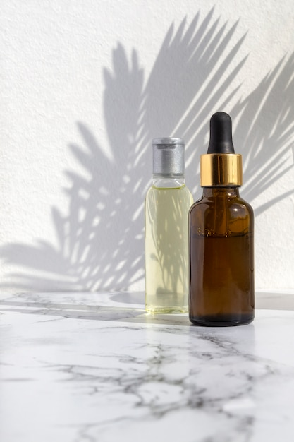 Cosmetic skincare products on marble background with palm leaves shadow. Premium Photo