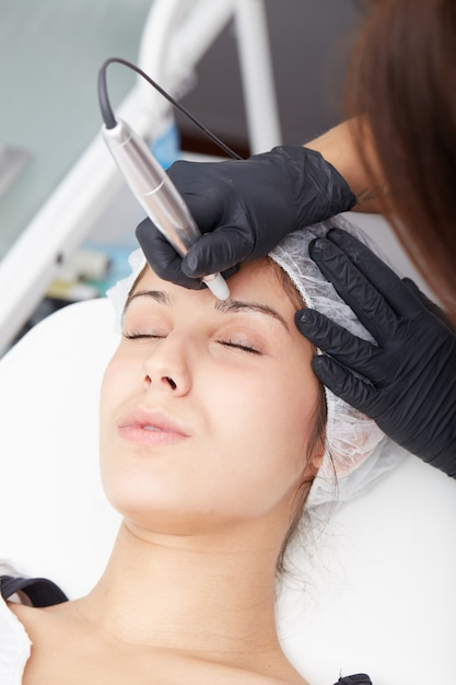 Cosmetician apply permanent make up on eyebrows Premium Photo