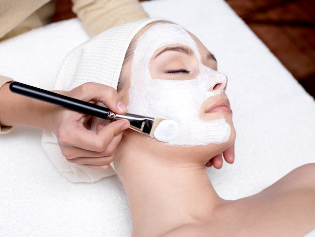 Cosmetician applying facial beauty mask for young beautiful woman at spa salon Free Photo