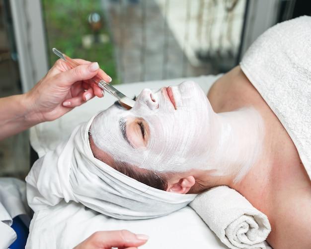 Косметолог, применяя маску для лица на лице женщины с палкой Premium Фотографии
