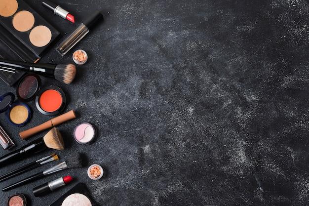 Cosmetics arranged on dusty dark background Free Photo