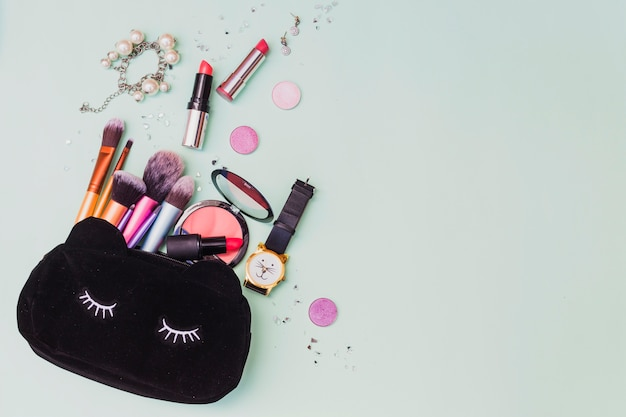 Cosmetics bag with bracelet; wristwatch and earrings on colored backdrop Free Photo