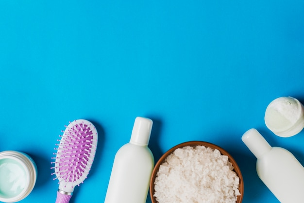 Cosmetics bottles; cream; hairbrush and salt on blue backdrop Free Photo