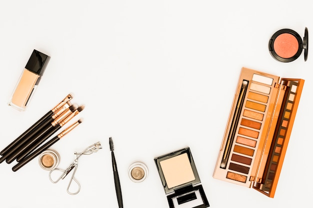 Cosmetics makeup palette with brushes and eyelashes curler isolated on white background Free Photo