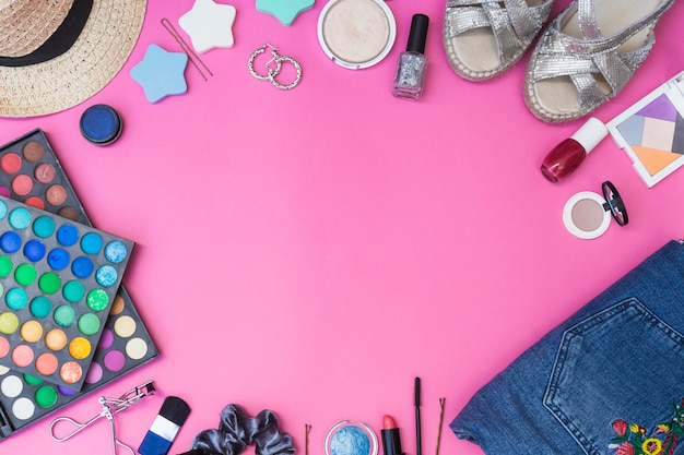 Cosmetics products; pair of footwear; clothes and hat on pink background Free Photo