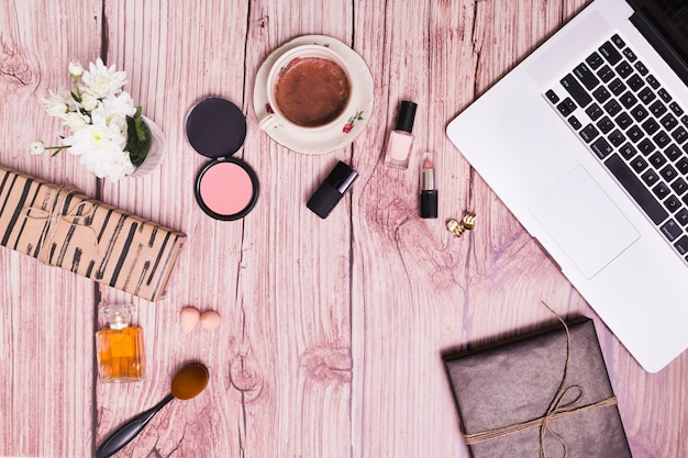 Cosmetics products; vase; diary and laptop on pink wooden textured background Free Photo