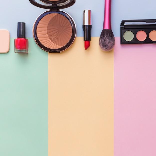 Cosmetics sponge; nail varnish bottle; lipstick; blusher and eye shadow palette on mixed colored background Free Photo