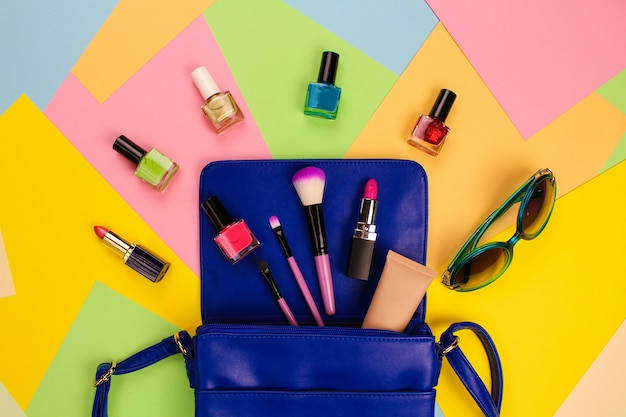 Cosmetics and women's accessories fell out of blue handbag Premium Photo