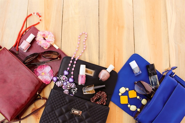 Cosmetics and women's accessories fell out of different handbag. things from open lady handbag. Premium Photo