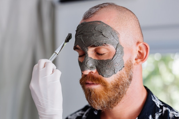 Cosmetologist apply clay mask with brush on young handsome mans face in beauty clinic Free Photo