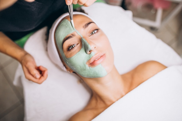Cosmetologist applying mask on a face of client in a beauty salon Free Photo
