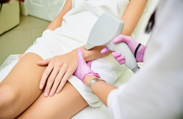 A cosmetologist carries out a procedure for laser hair removal from the body of a girl. laser hair removal. cosmology. hand hair removal Premium Photo