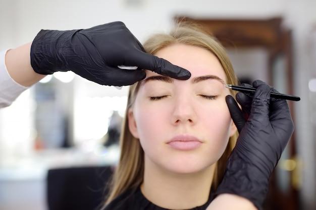 Косметолог выщипывание бровей. привлекательная женщина, получать уход за лицом и макияж в салоне красоты. архитектура бровей. Premium Фотографии