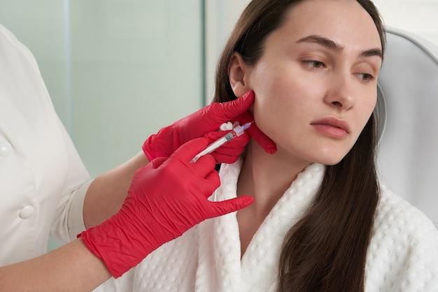 Косметолог делает липолитические уколы для сжигания жира на подбородке против двойного подбородка. Premium Фотографии
