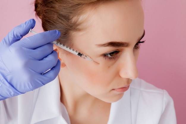 Cosmetologist making injection to a client Premium Photo