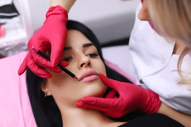 Cosmetologist making permanent makeup on woman's face Photo