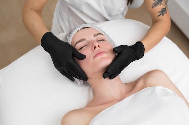 美容師が少女の顔にヒアルロン酸をこすりつける Premium写真