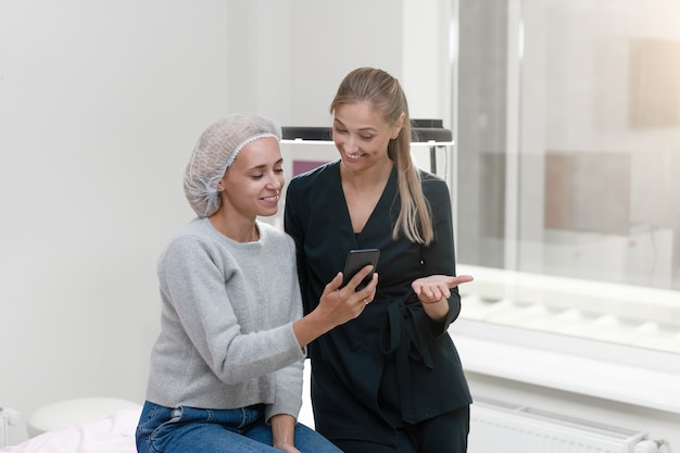 Клиент кабинета косметологии, сидя на диване. косметолог показывает дисплей смартфона Premium Фотографии