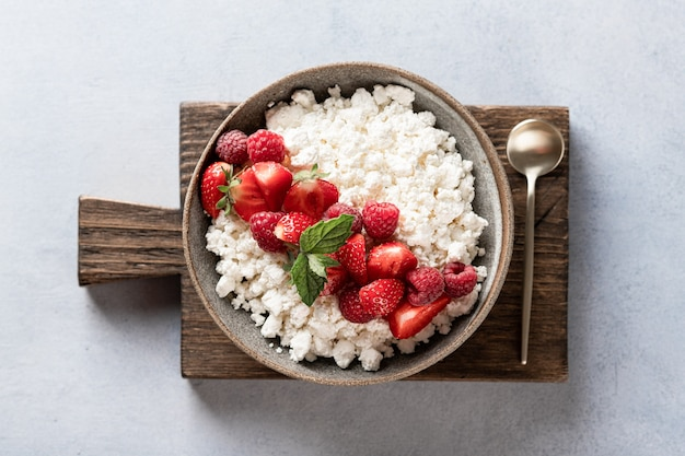 Cottage cheese bowl with berries on a light background, top view Premium Photo
