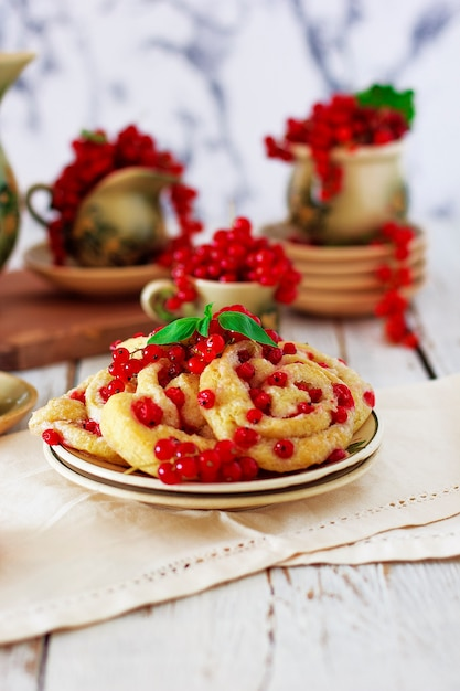 Cottage cheese cookie rolls with red currants on ceramic plate with vintage ceramic tea or coffee set, tea time, breakfast, summer sweets Free Photo