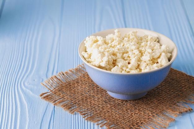 파란 나무 배경에 그릇에 코 티 지 치즈를 닫습니다. 프리미엄 사진