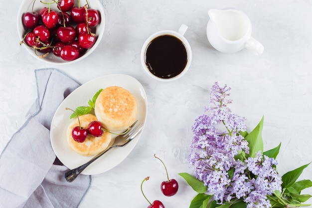 Cottage cheese pancakes, cup of black coffee, milk and bowl Premium Photo
