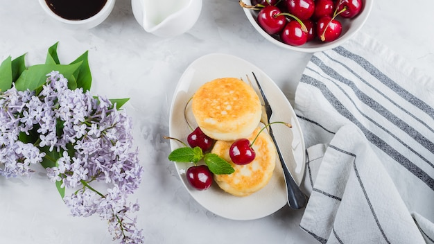 Cottage cheese pancakes with berry cherry, cup of black coffee Premium Photo
