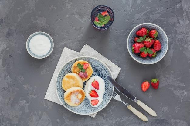 Творожные оладьи со сметаной и клубникой на завтрак или обед на сером. вид сверху Premium Фотографии