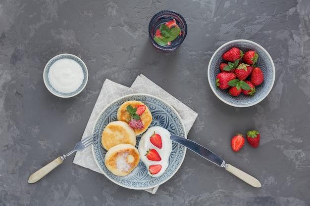 Творожные оладьи со сметаной и клубникой на завтрак или обед на сером. Premium Фотографии