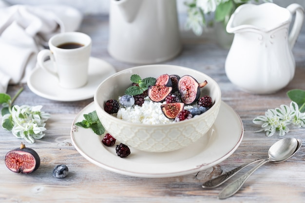 Cottage cheese with figs, berries, honey. cup of coffee and coffee pot. breakfast. wooden table. Premium Photo
