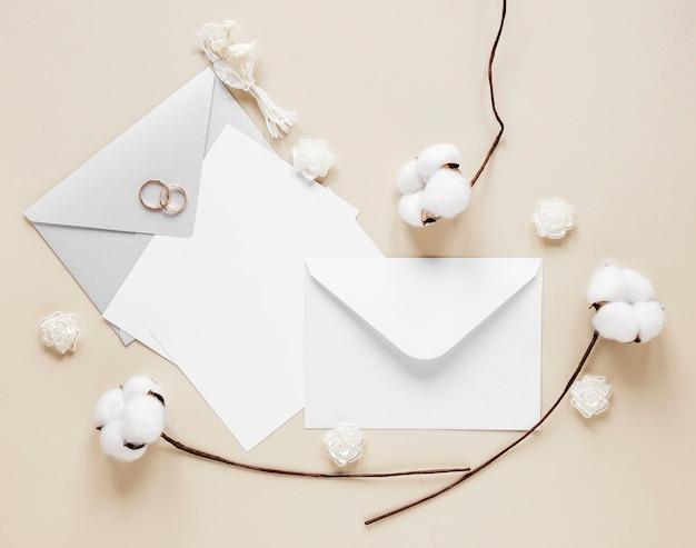 結婚式の招待状の横にある綿の枝 Premium写真