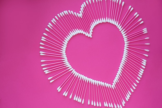 Cotton buds laid out in the shape of a heart on a pink background Premium Photo