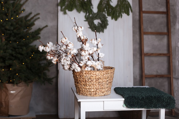 Cotton flowers in a basket. scandinavia. delicate white cotton flowers. cotton flowers in interior of house. dried white fluffy cotton in a basket on table. rustic home interior. christmas. new year. Premium Photo