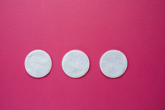 Cotton swabs and disks isolated on a pink background. hygiene products. Premium Photo