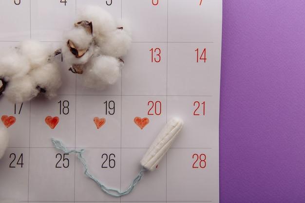 ライラックの背景に綿タンポンとカレンダー。女性の危機的な日々のための衛生保護。 Premium写真