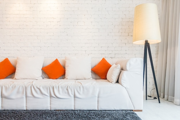 Couch with cushions and floor lamp Free Photo