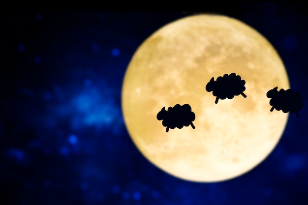 Counting sheep silhouette over a full moon Free Photo