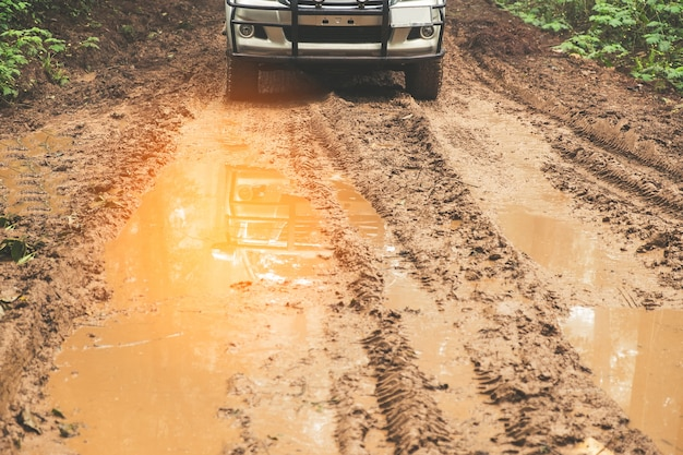 Countryside landscape with car on muddy road Premium Photo